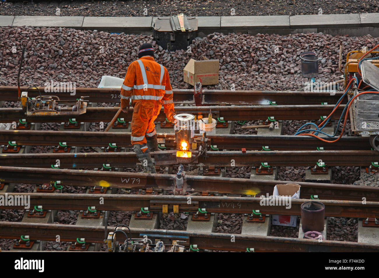 A track worker having just lit a Rail welder device that melts the two track together to for a continuous line in - Stock Image