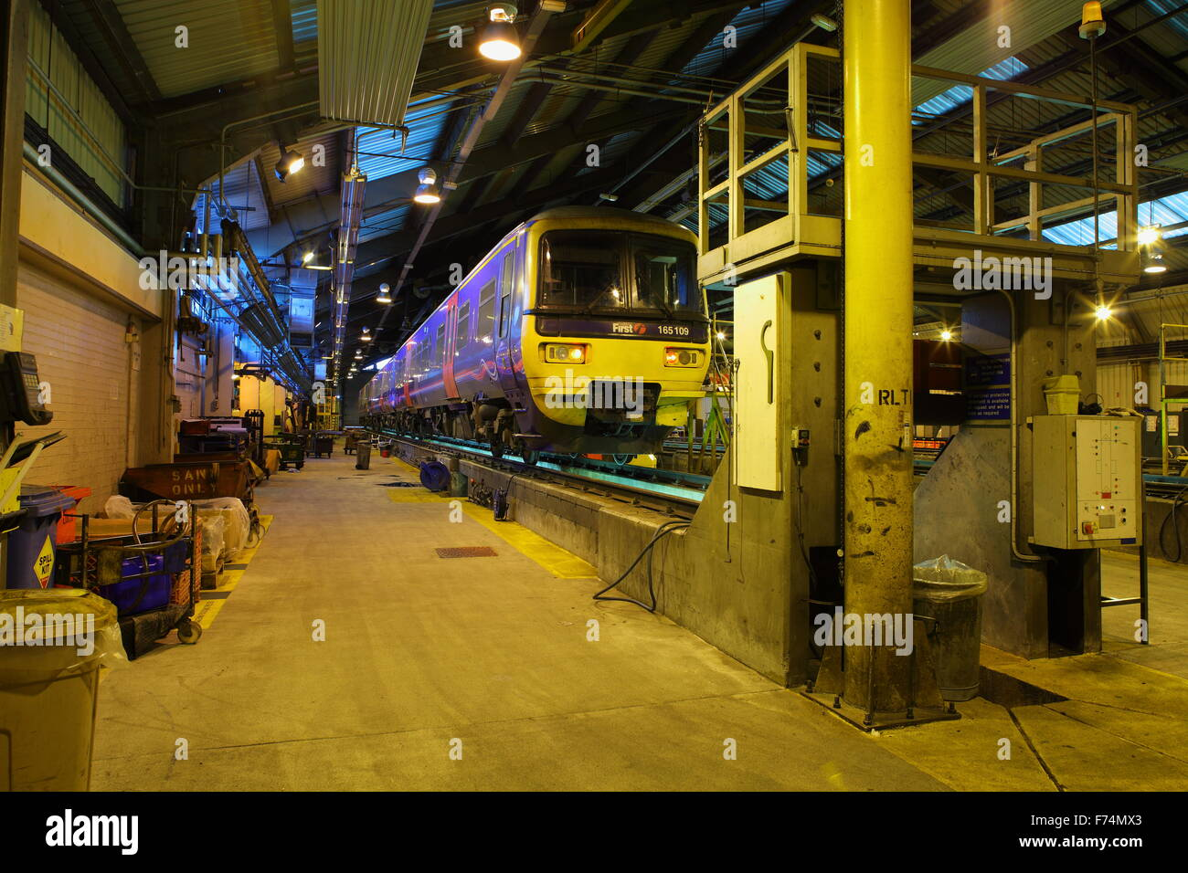 Looking down the side of a Diesel Multiple unit raised high on elevated rails awaiting servicing in a long shed - Stock Image