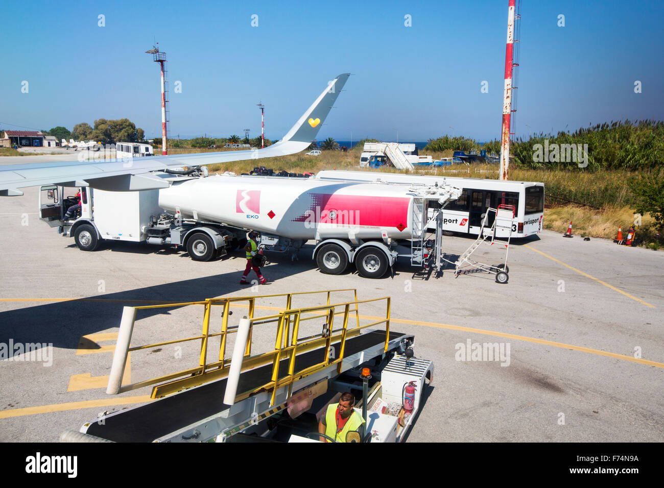 Baggage handlers and a refuelling tanker at Mytilene airport on Lesvos, Greece. Stock Photo