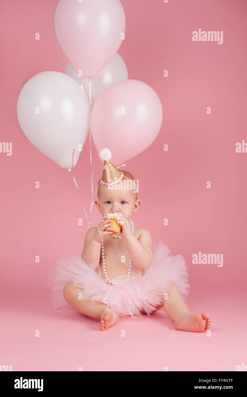 A Portrait Of One Year Old Baby Girl Wearing Pink Tutu String Pearls And Birthday Hat She Is Sitting Eating Cupca