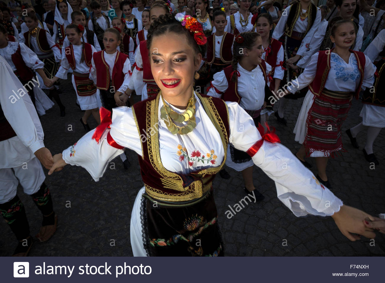 """Serbian girl dressed in national costume dances traditional folklore dance """"Kolo"""". Central square in Sabac, Serbia. Stock Photo"""