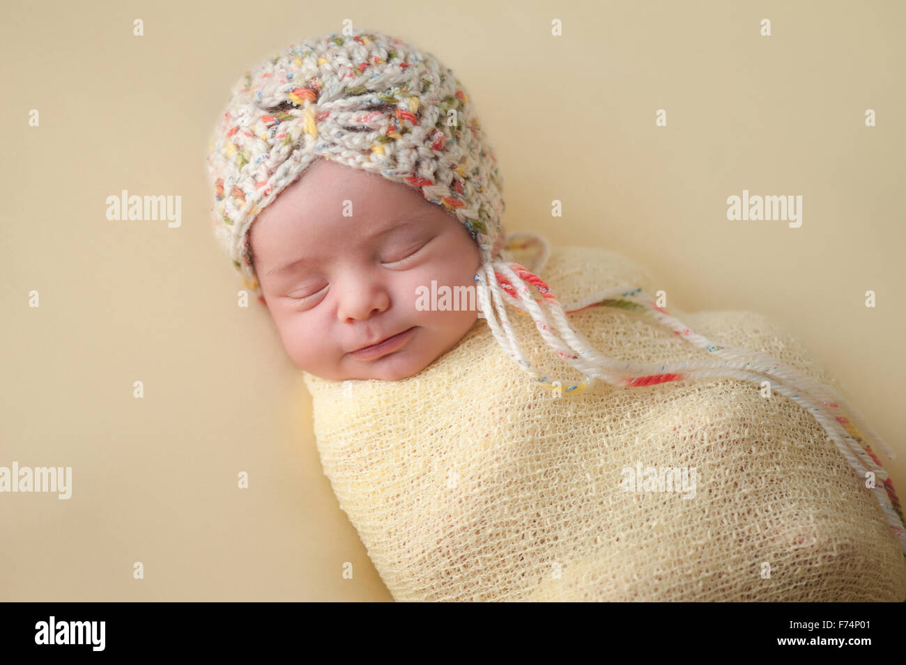 A portrait of a beautiful, two week old, newborn baby girl wearing a  crocheted bonnet. She is smiling and sleeping on yellow col 03aa80c915d
