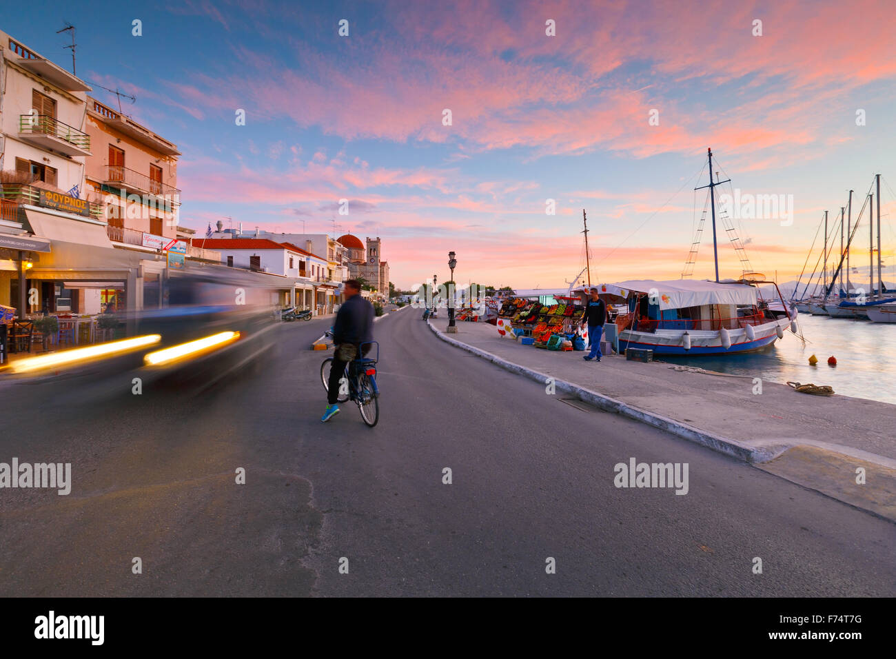Cyclist in a crossroad at the seafront of Aegina town and the view of the main harbour of the island, Greece - Stock Image