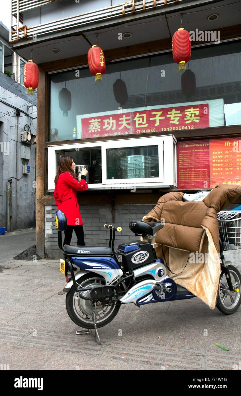 Young woman at Beijing hutong food shop - Stock Image