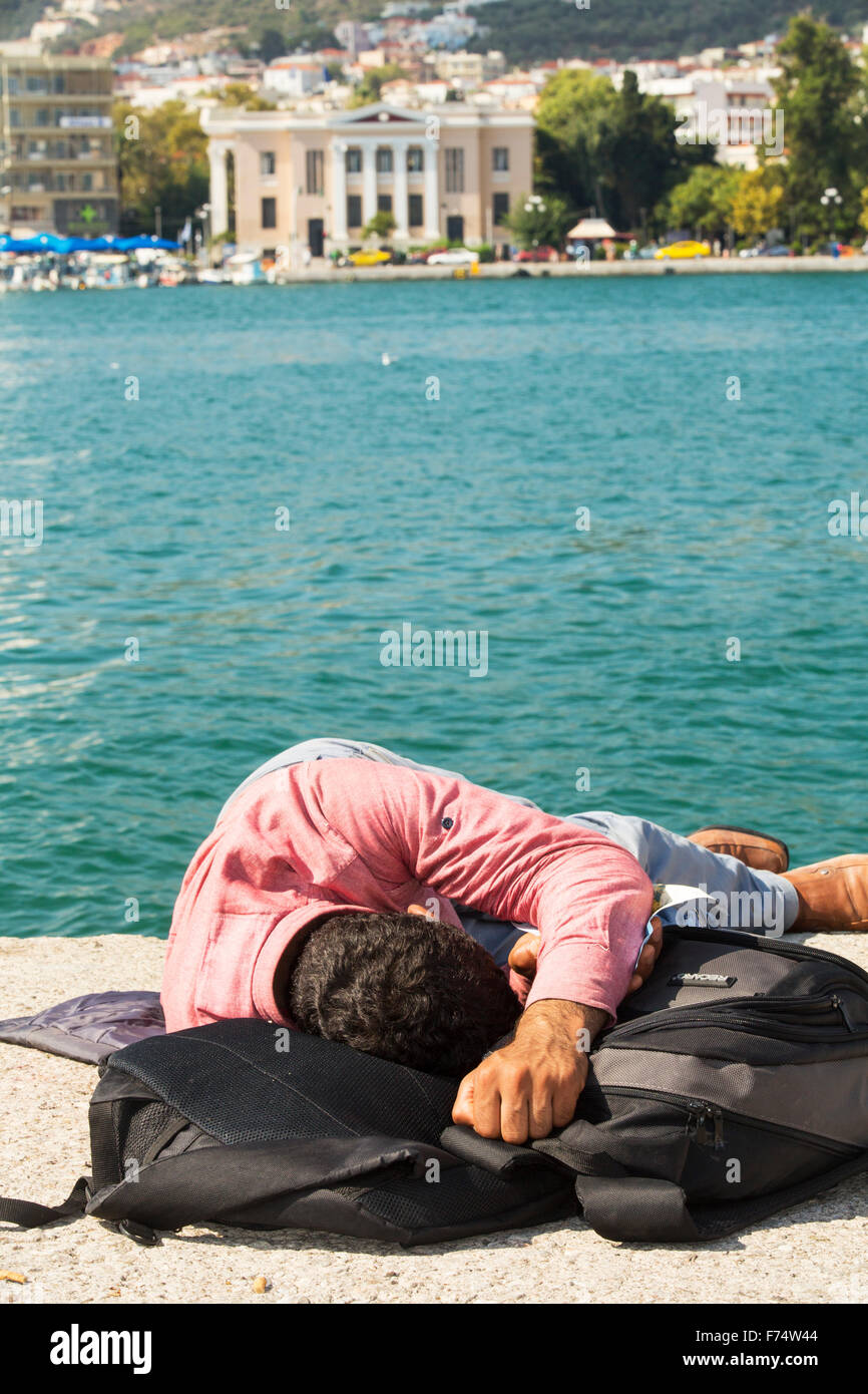 An exhausted Syrian migrantthat is fleeing the war and escaping to Europe, who has landed on the Greek island of Stock Photo