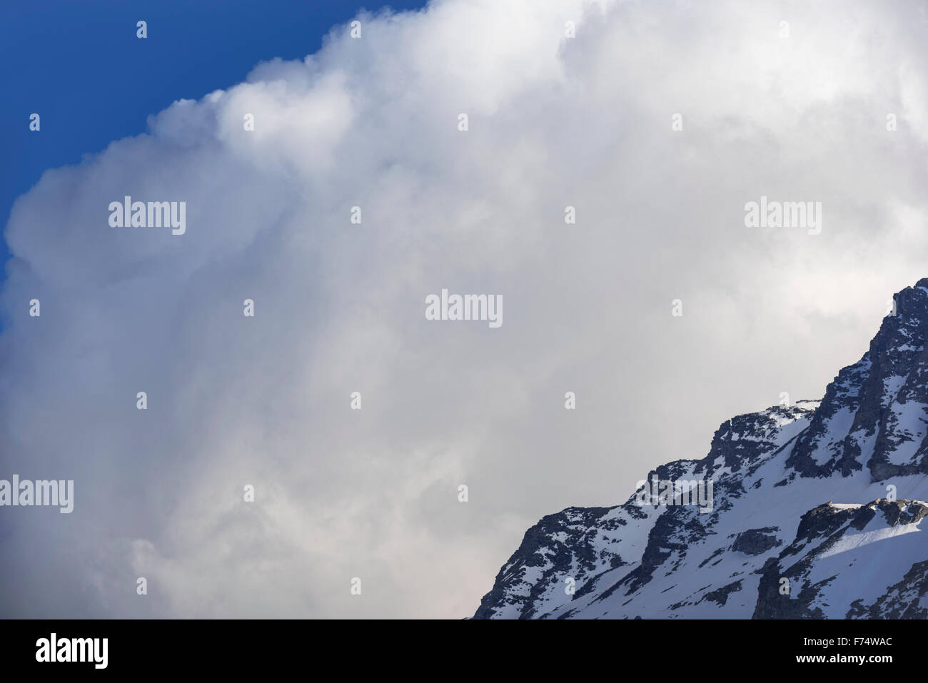 Cumulonimbus cloud developping behind mountain in the Alps - Stock Image