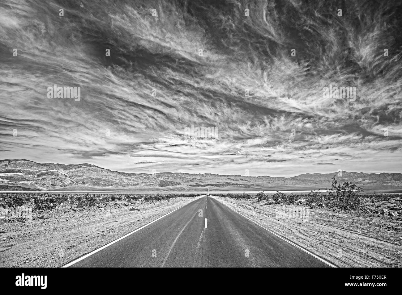 Black and white photo of a country highway in Death Valley, California, USA. - Stock Image