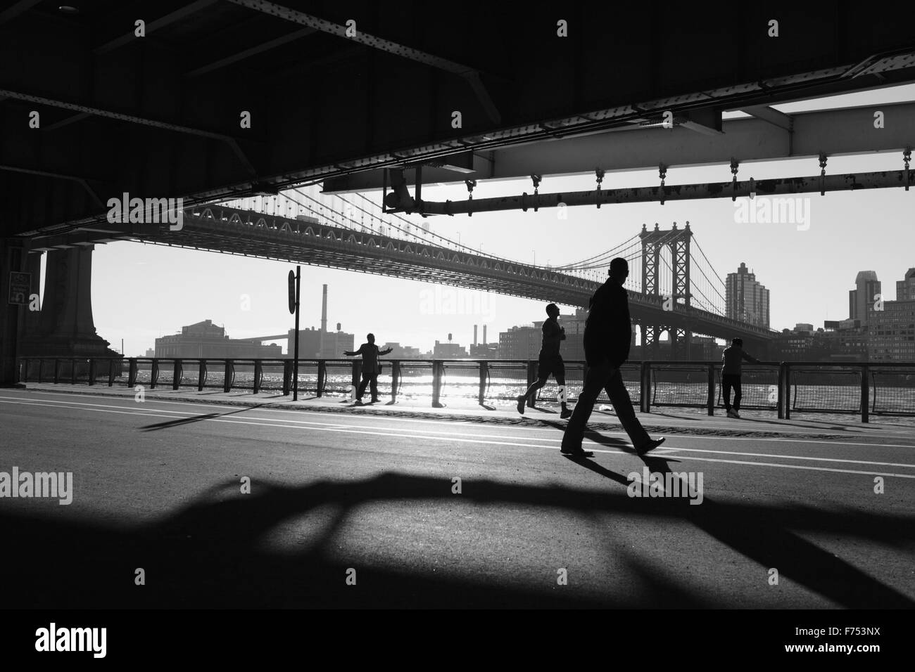 Two Chinatown women exercise, a man runs, another walks while watching the others along the East River overpass - Stock Image