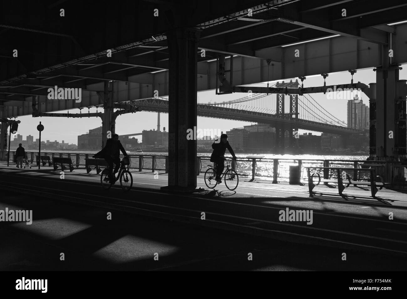 Two men cycle and another walks along the East River Esplanade, New York - Stock Image