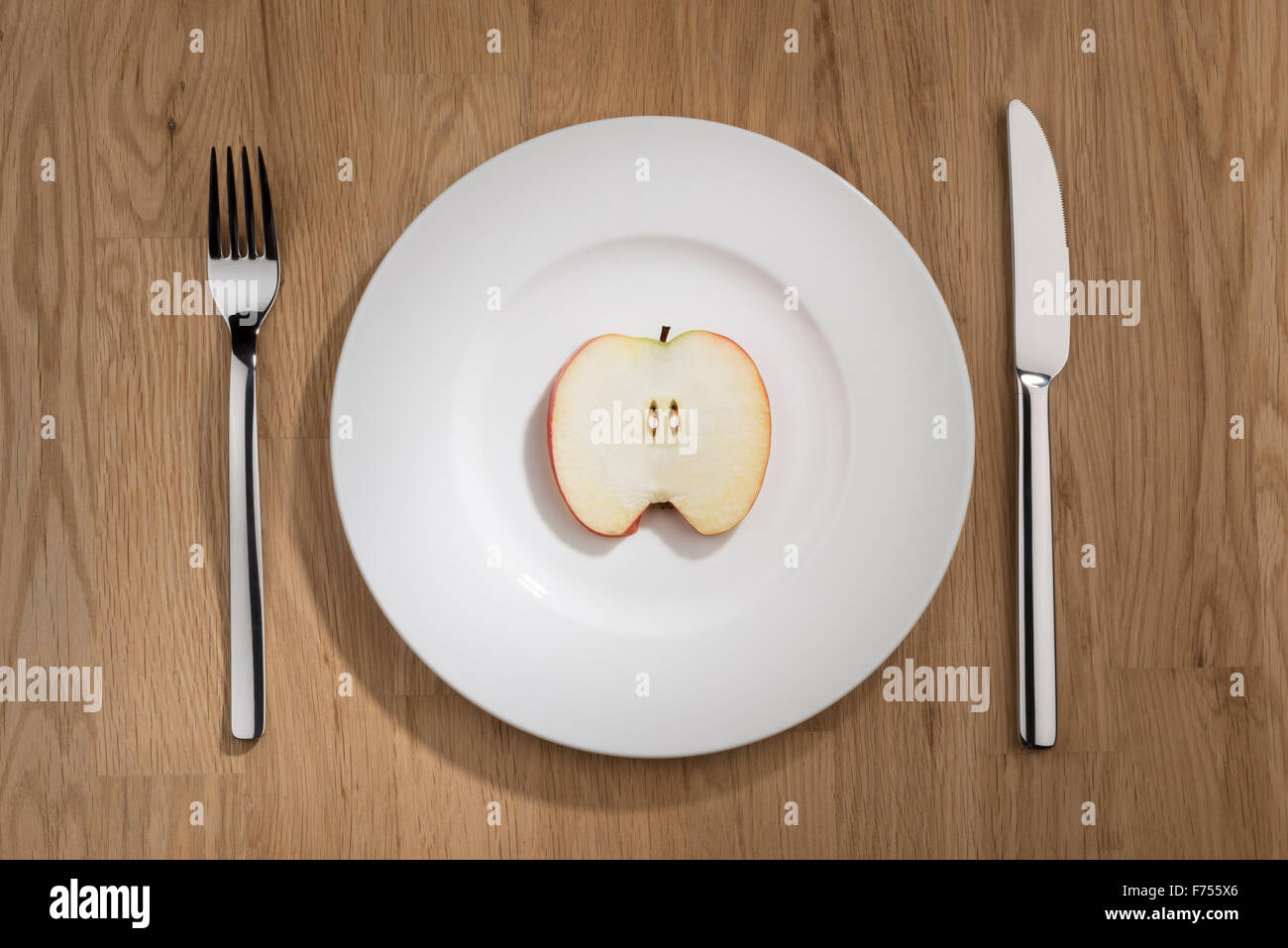 Image of a apple slice on a white plate with fork and knife - Stock Image