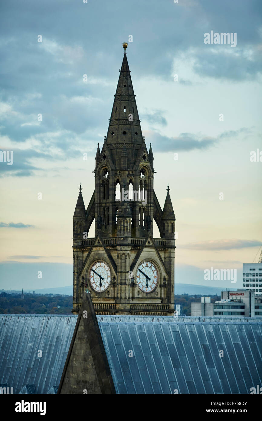 Manchester skyline showing the rooftops and the clock tower of the town hall    tower light shaft rays through clouds Stock Photo