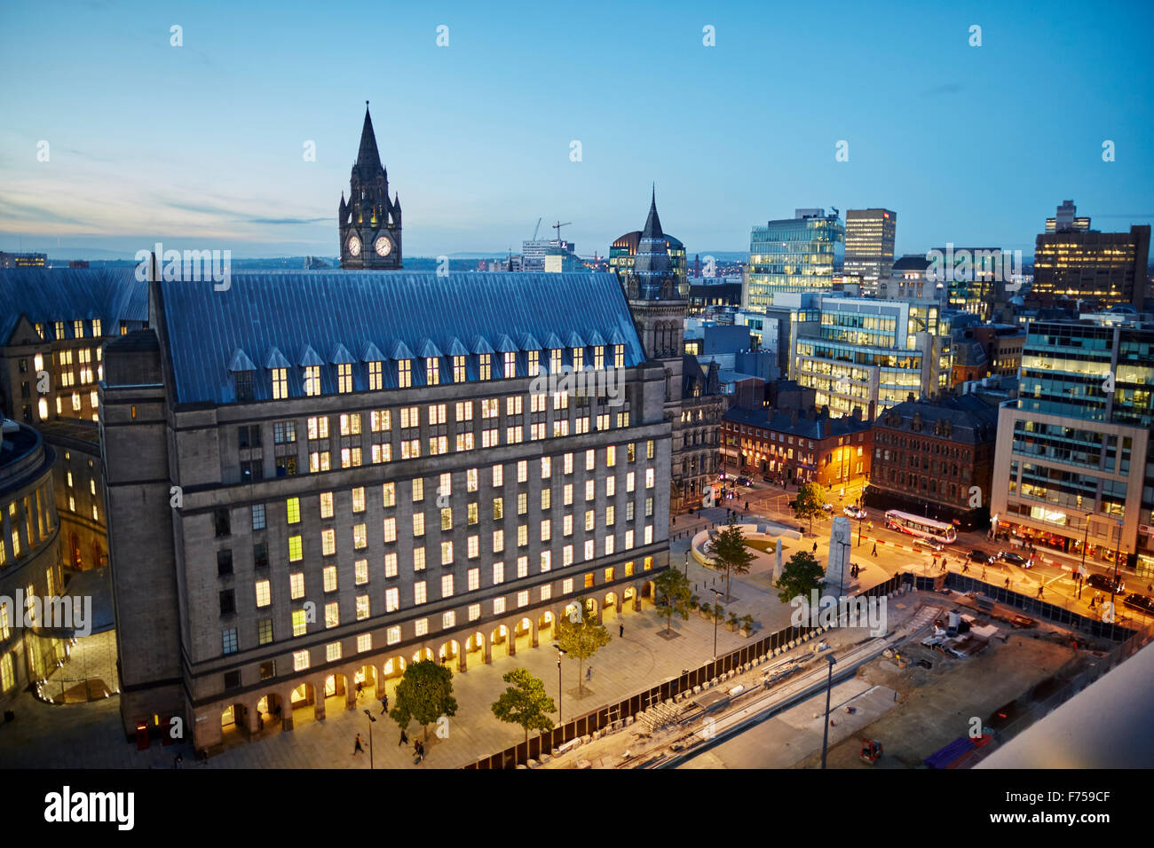 Manchester skyline showing the rooftops and central library and the town hall extension    tower light shaft rays through clouds Stock Photo