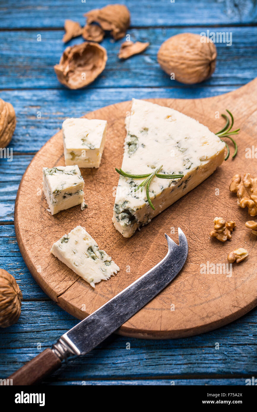 Tasty blue cheese with nut on wooden cutting board - Stock Image