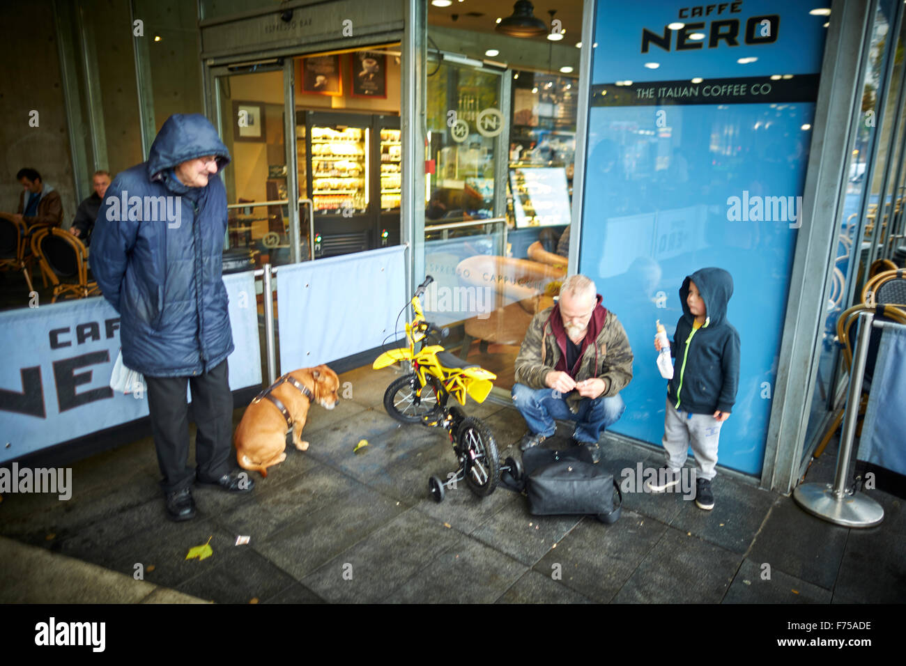 Cafe Nero caffe outside young boy bike waiting dog eating being watched happy Piccadilly Gardens Manchester  Man - Stock Image