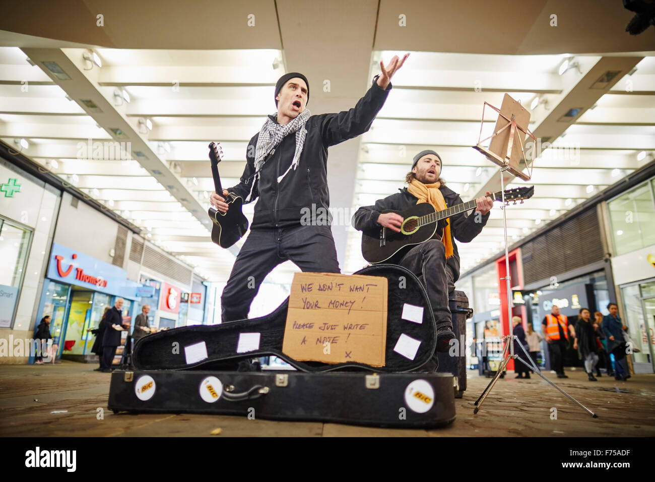 Busking buskers performance performing performer entertaing passing people crowds singing card no money   two shopping - Stock Image