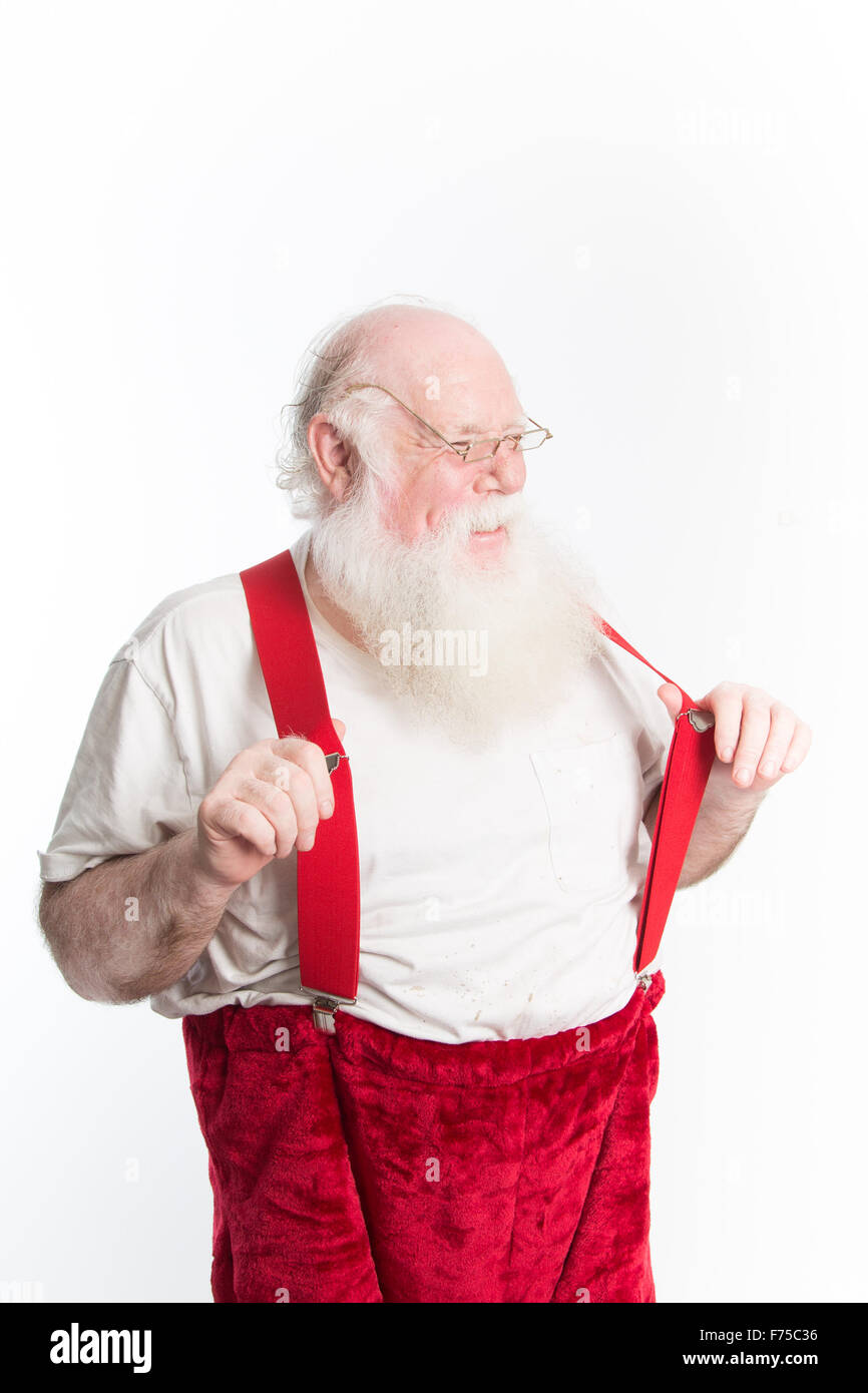 A laughing Santa Claus in under shirt and red suspenders as he dresses for Christmas eve - Stock Image
