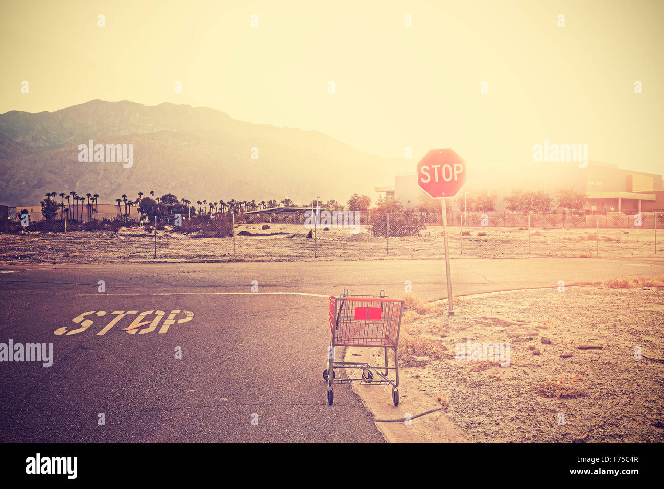 Retro toned empty shopping trolley left on street at sunset, Palm Springs, USA. - Stock Image