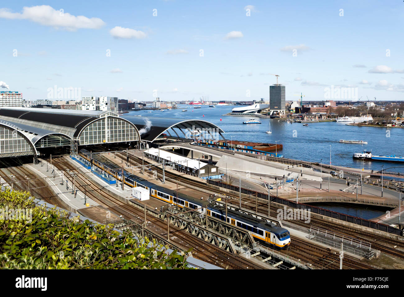 Image of IJ River & part of the railway station Amsterdam viewed from the rooftop of the Doubletree Hotel - Stock Image