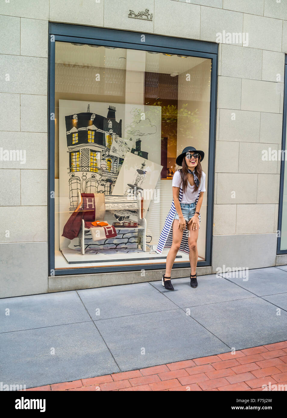 A young Asian adult woman having fun, smiling and pretend modeling in front of a high end San Francisco store window. - Stock Image