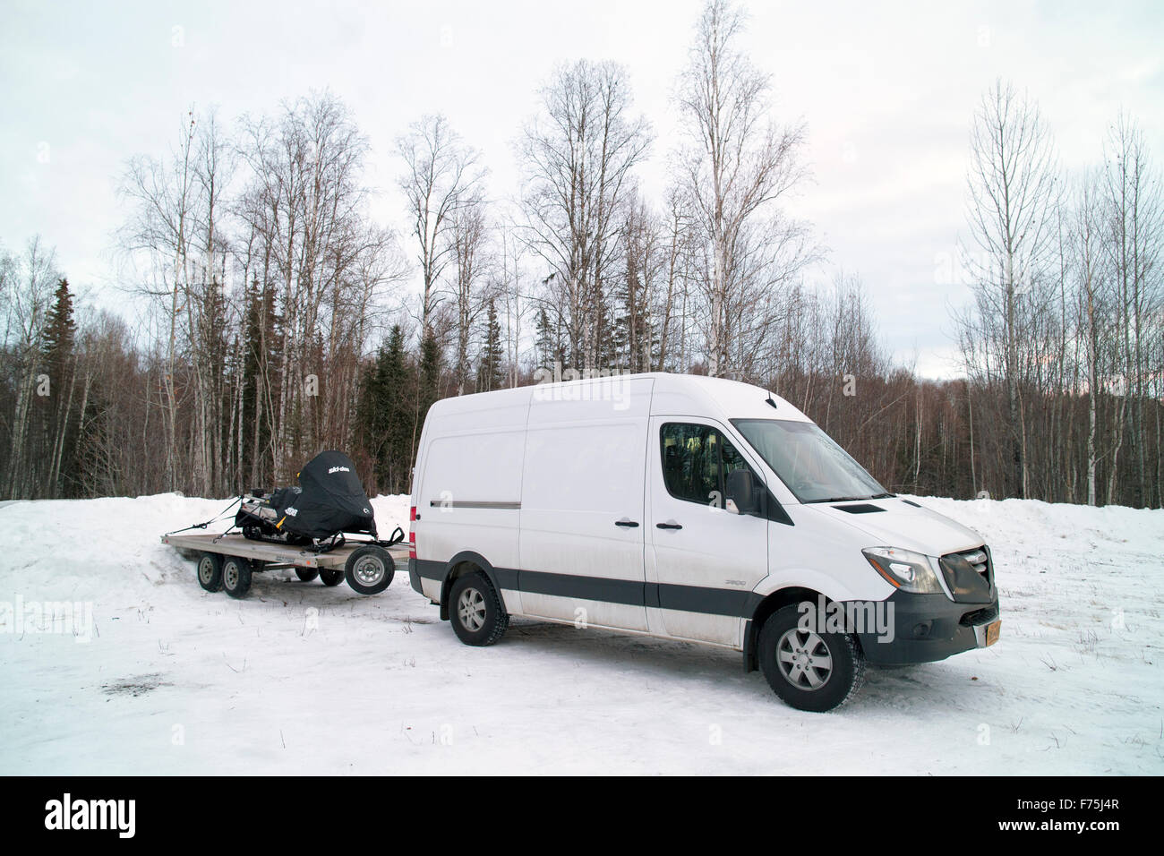 The new Freightliner Sprinter Cargo Van short hi-roof pulling a snowmachine trailer during the winter in Alaska - Stock Image