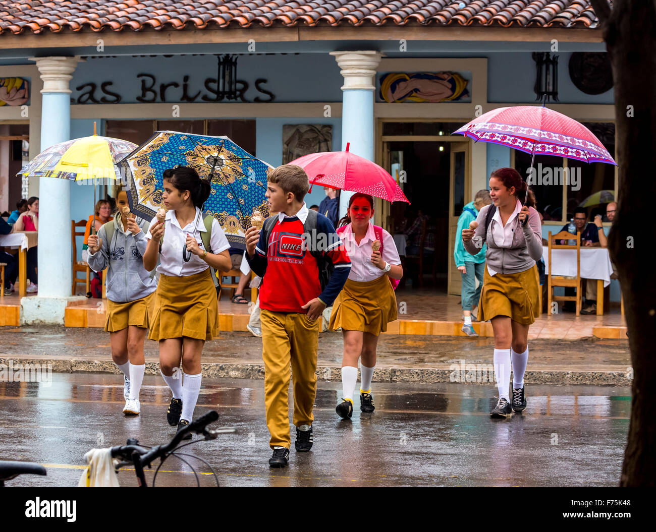 Schoolchildren, students cross a road in Vinales, rain, umbrellas, eating ice cream, Viñales, Cuba, Pinar del - Stock Image