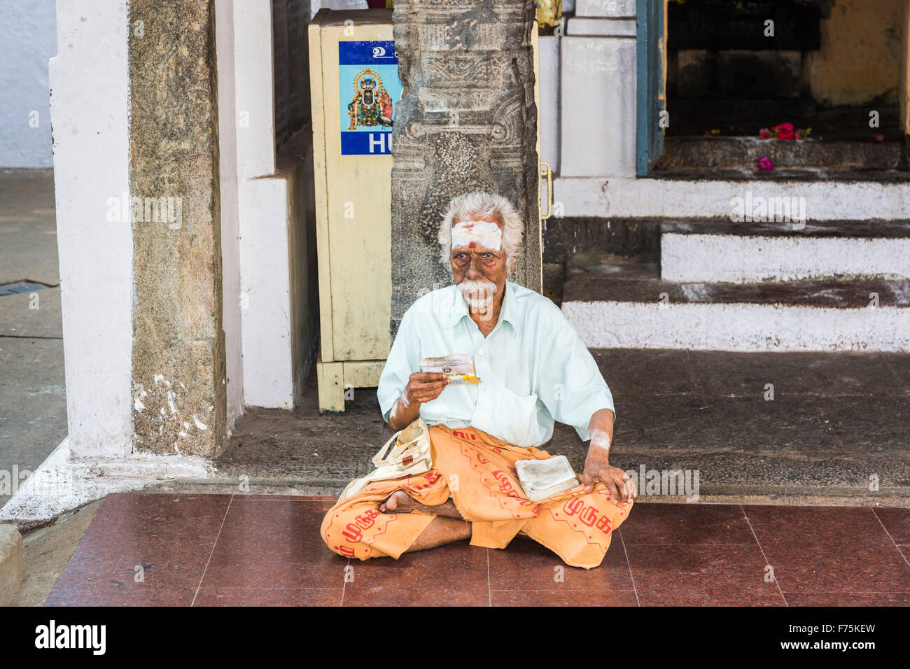 Sadhu holy man sitting outside a shrine in Kapaleeswarar Temple, a Hindu temple of Shiva located in Mylapore, Chennai, - Stock Image