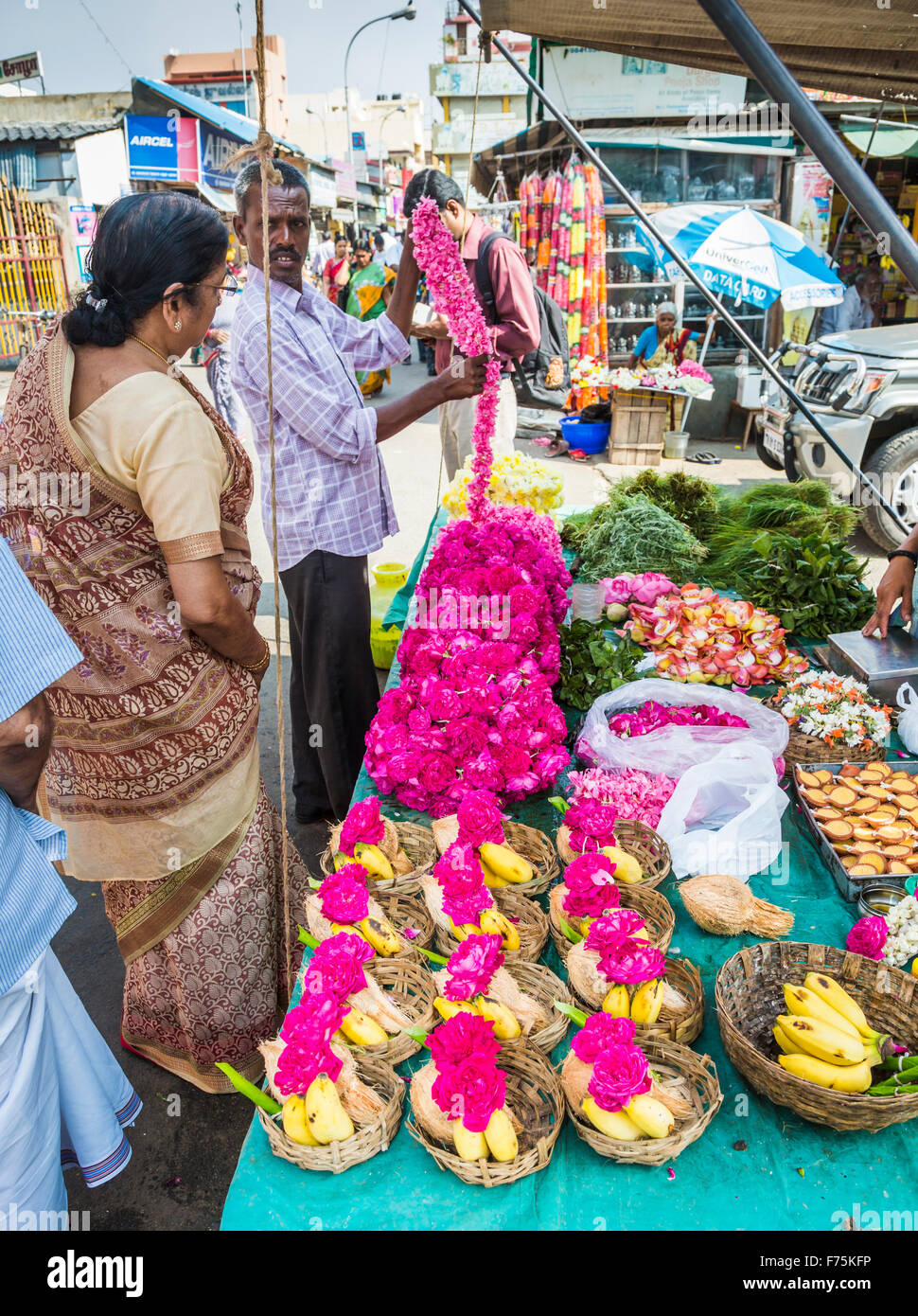 Flower seller selling garlands for temple offerings outside Kapaleeswarar Temple, a Hindu temple of Shiva located - Stock Image