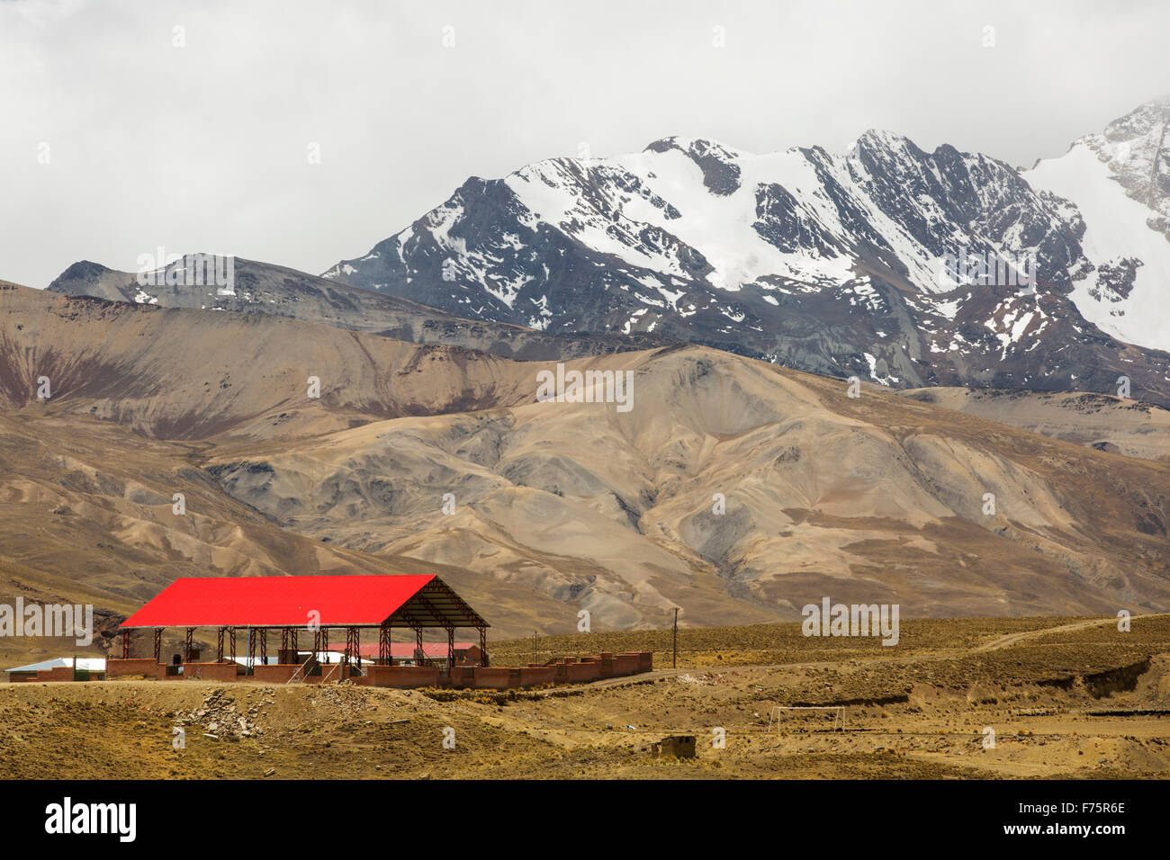 Looking over the Altiplano to the snow covered Andean peak of Huayna Potosi in Bolivia. - Stock Image