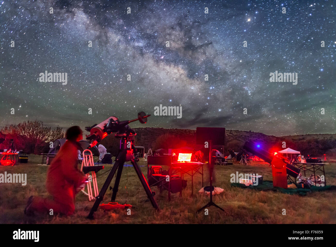 An observer at the Texas Star Party aims his telescope at a target in the Milky Way. Sagittarius and Scorpius toward - Stock Image