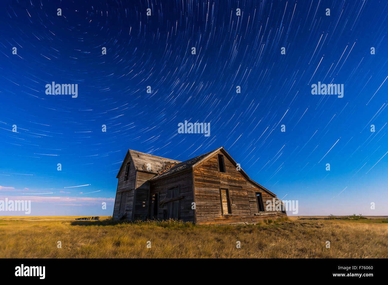 Circumpolar star trails circling above an old rustic and abandoned house near Bow Island, Alberta, with illumination - Stock Image