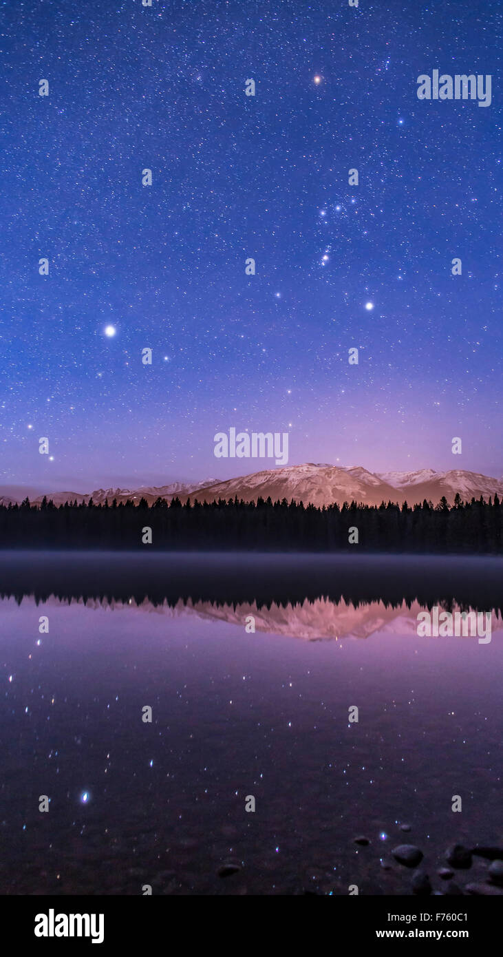 Orion and Canis Major over Lake Annette, in Jasper National Park, with Sirius and other stars reflected in the waters. - Stock Image