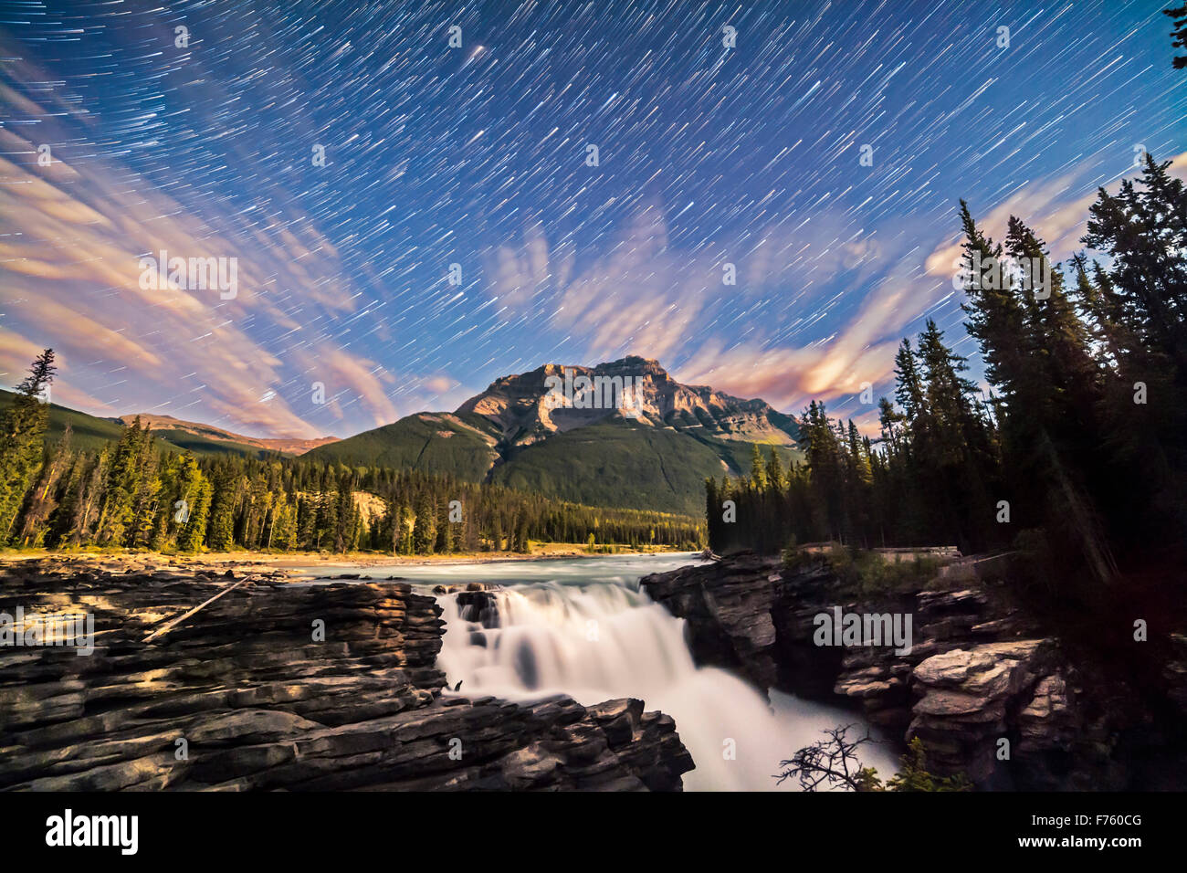 The stars of autumn rising over Mount Kerkeslin and Athabasca Falls in Jasper National Park, Alberta, on a night - Stock Image