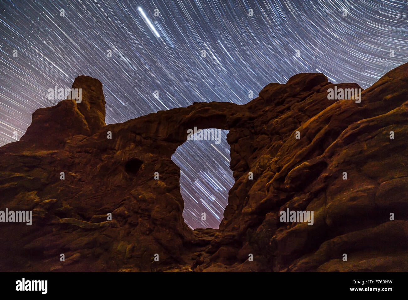 Orion and the stars of the winter sky trailing as they set behind and through Turret Arch, in Arches National Park, - Stock Image