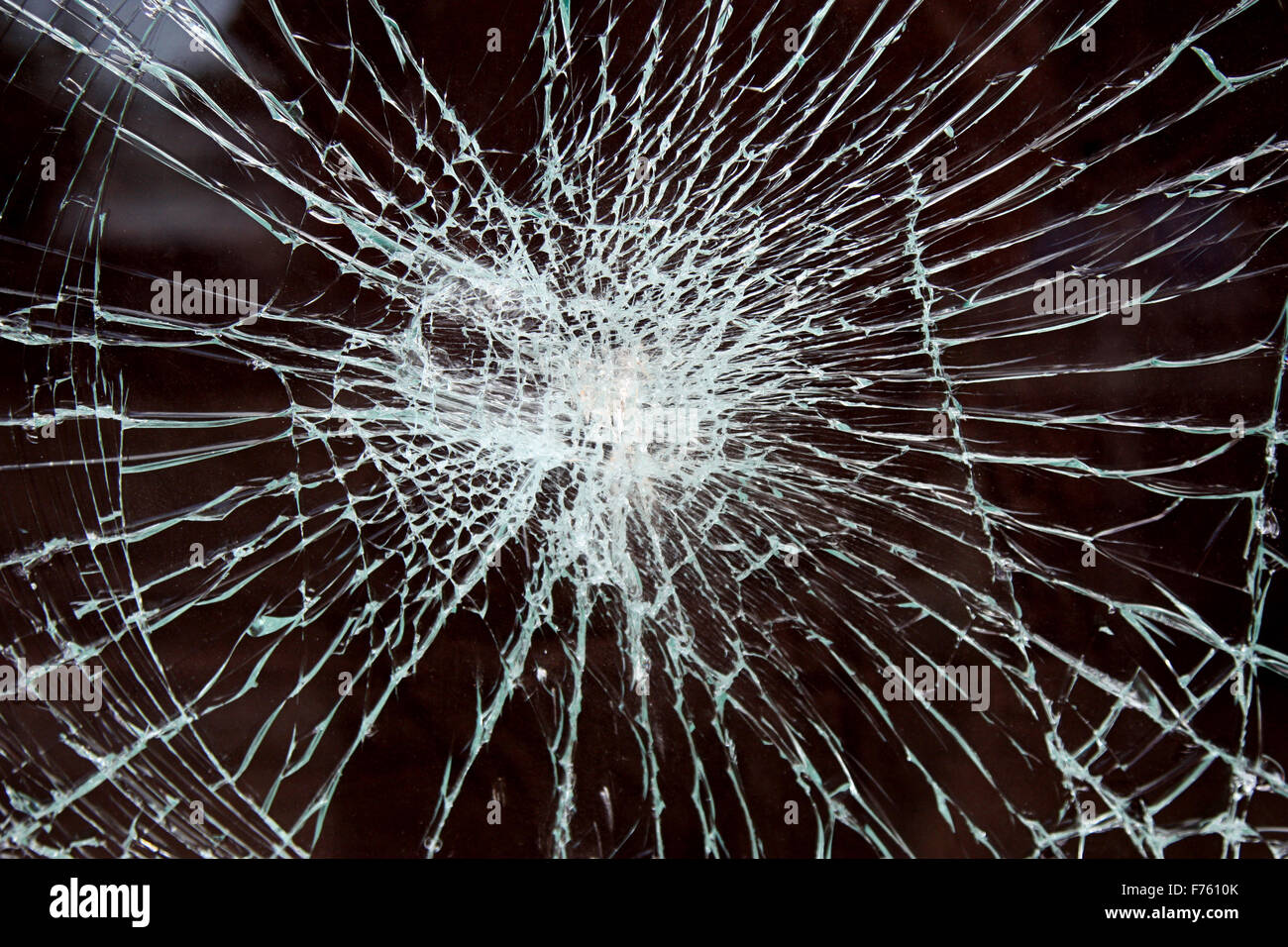 a smashed piece of glass on dark background - Stock Image