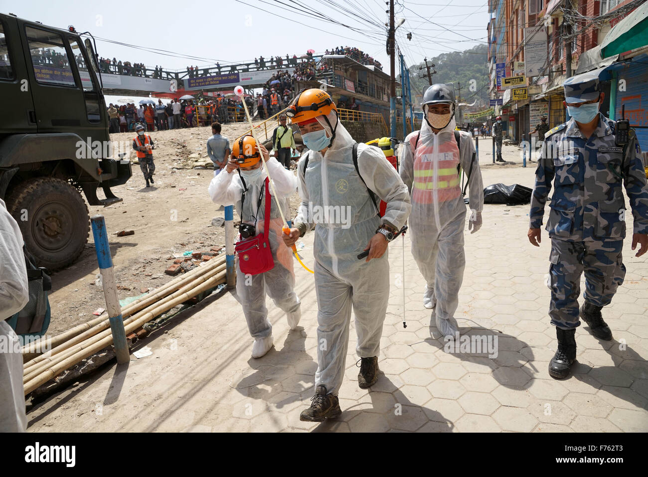 Rescue personnel spray disinfectant, earthquake, nepal, asia - Stock Image