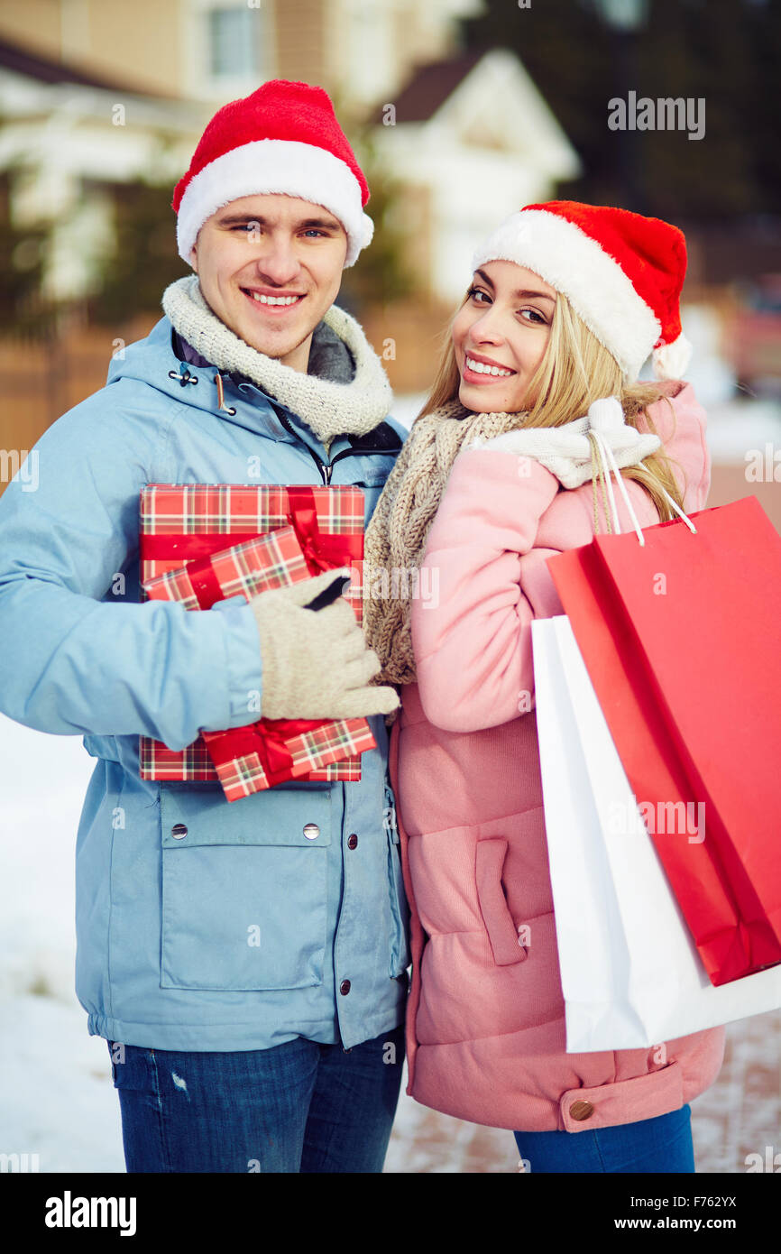 Cheerful young people doing Christmas shopping - Stock Image