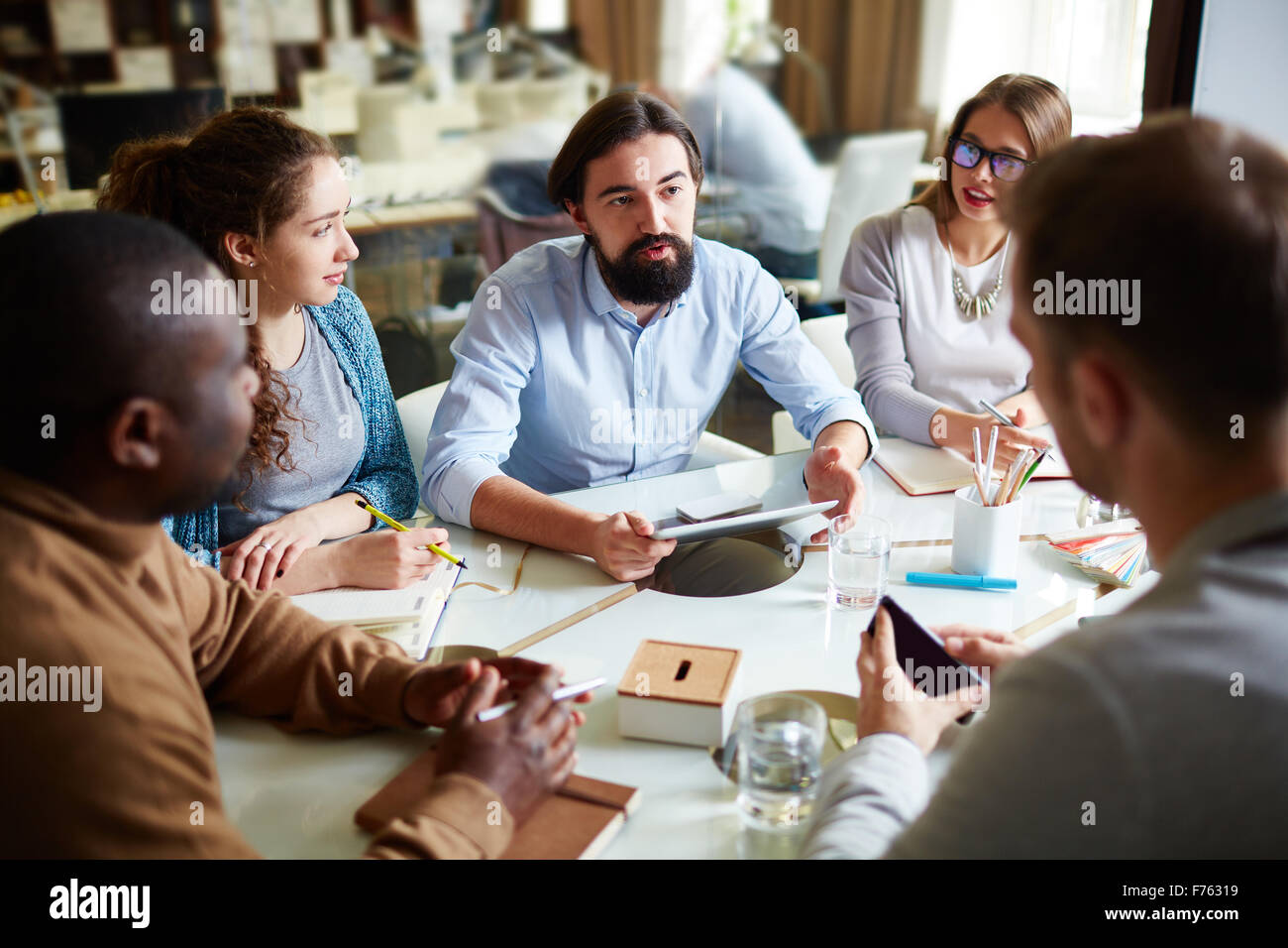 Group of office workers listening to colleague at meeting - Stock Image