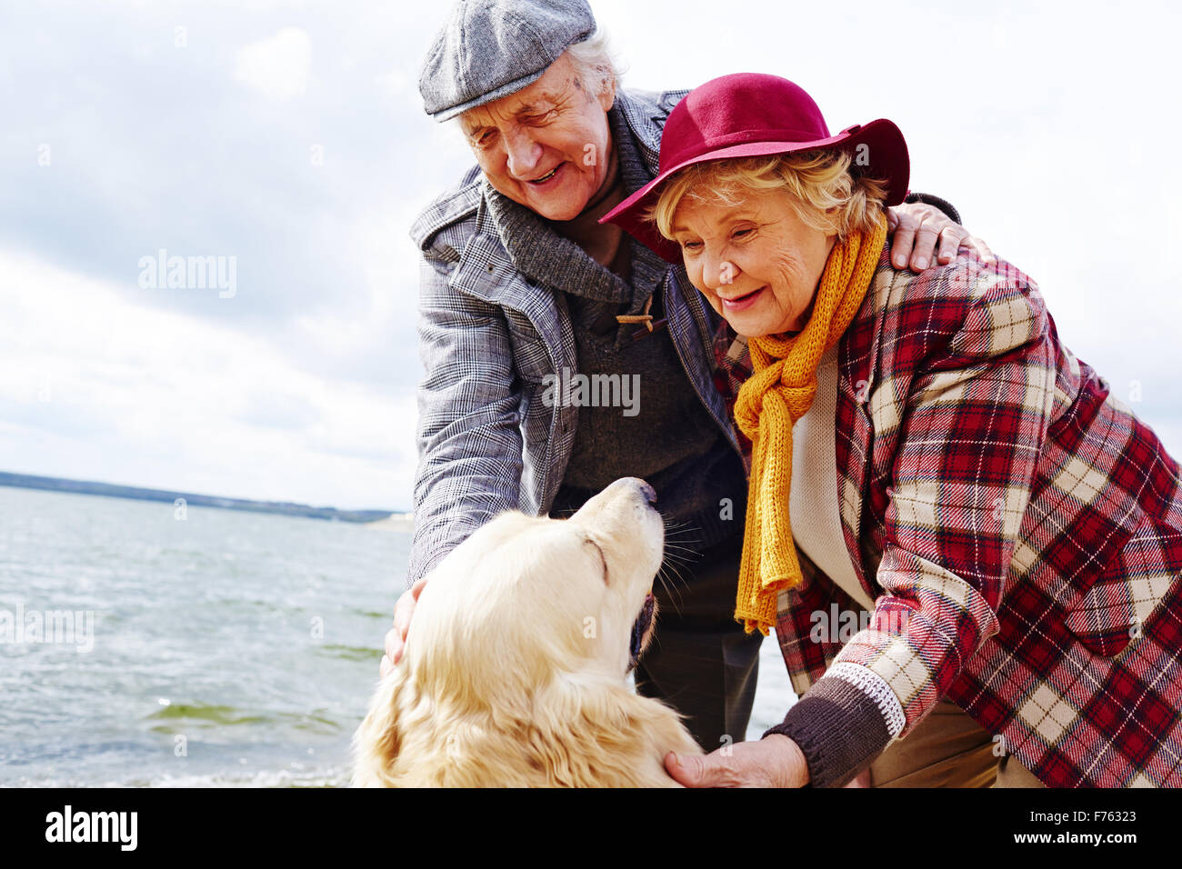 Retired couple cuddling their pet outdoors - Stock Image