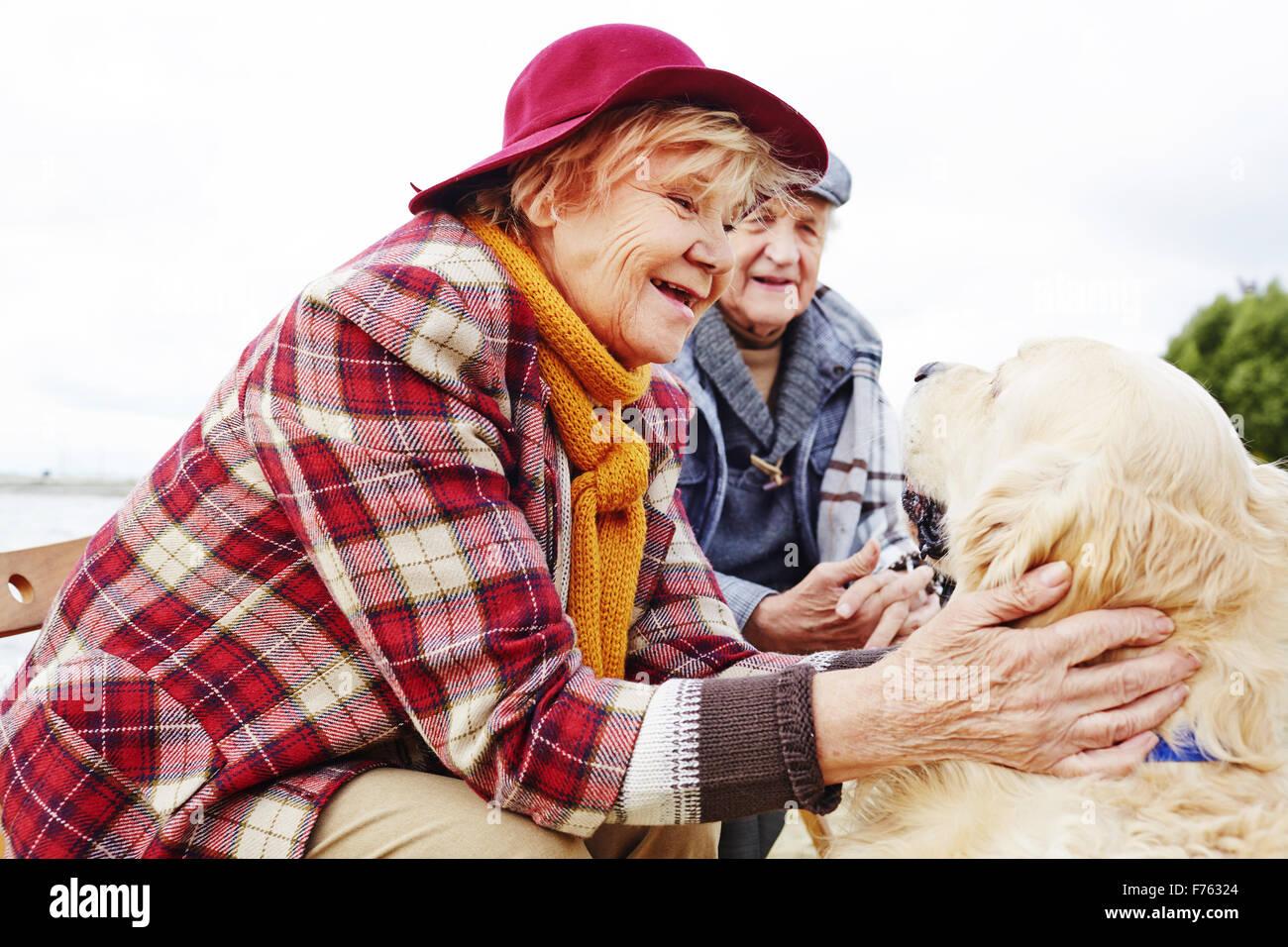 Retired female cuddling dog outdoors - Stock Image