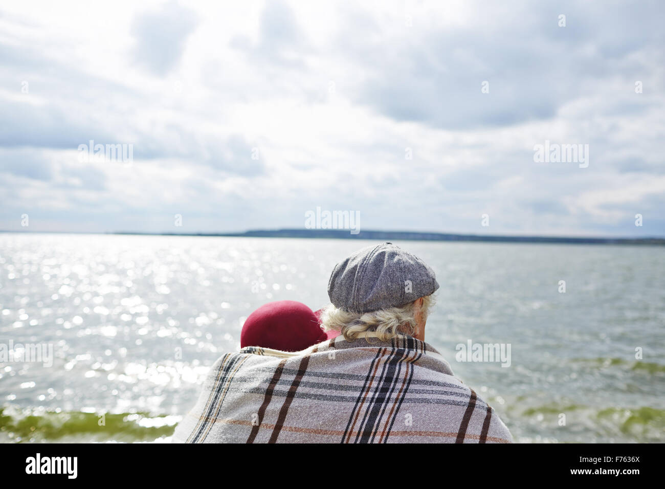 Back view of affectionate seniors view of seaside - Stock Image