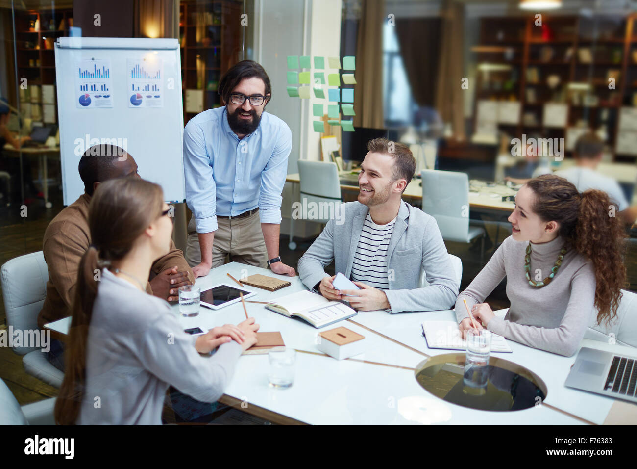 Happy modern office workers discussing plans and ideas at meeting - Stock Image