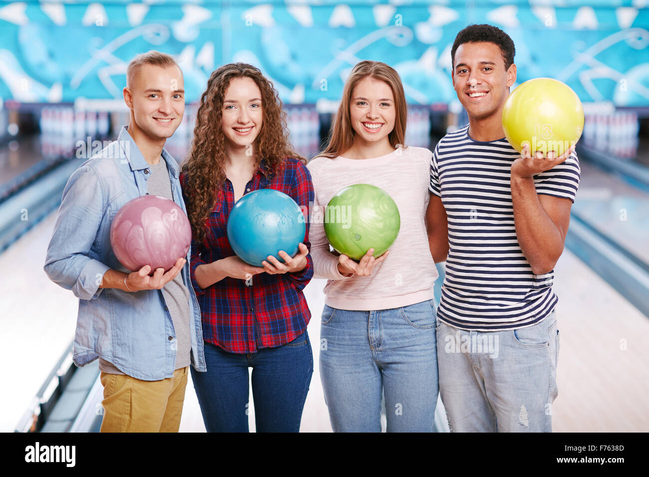 Group of four friends holding bowling balls and smiling - Stock Image