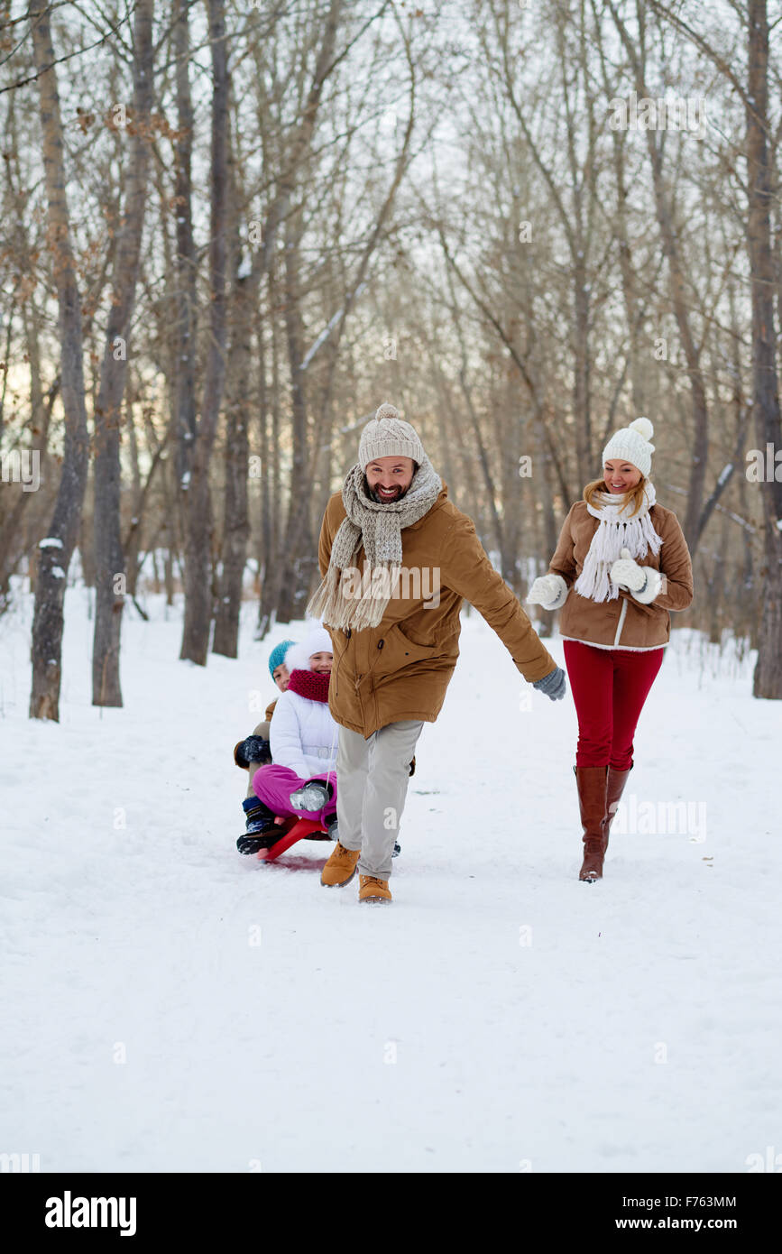 Happy man pulling sledge with kids in winter park - Stock Image