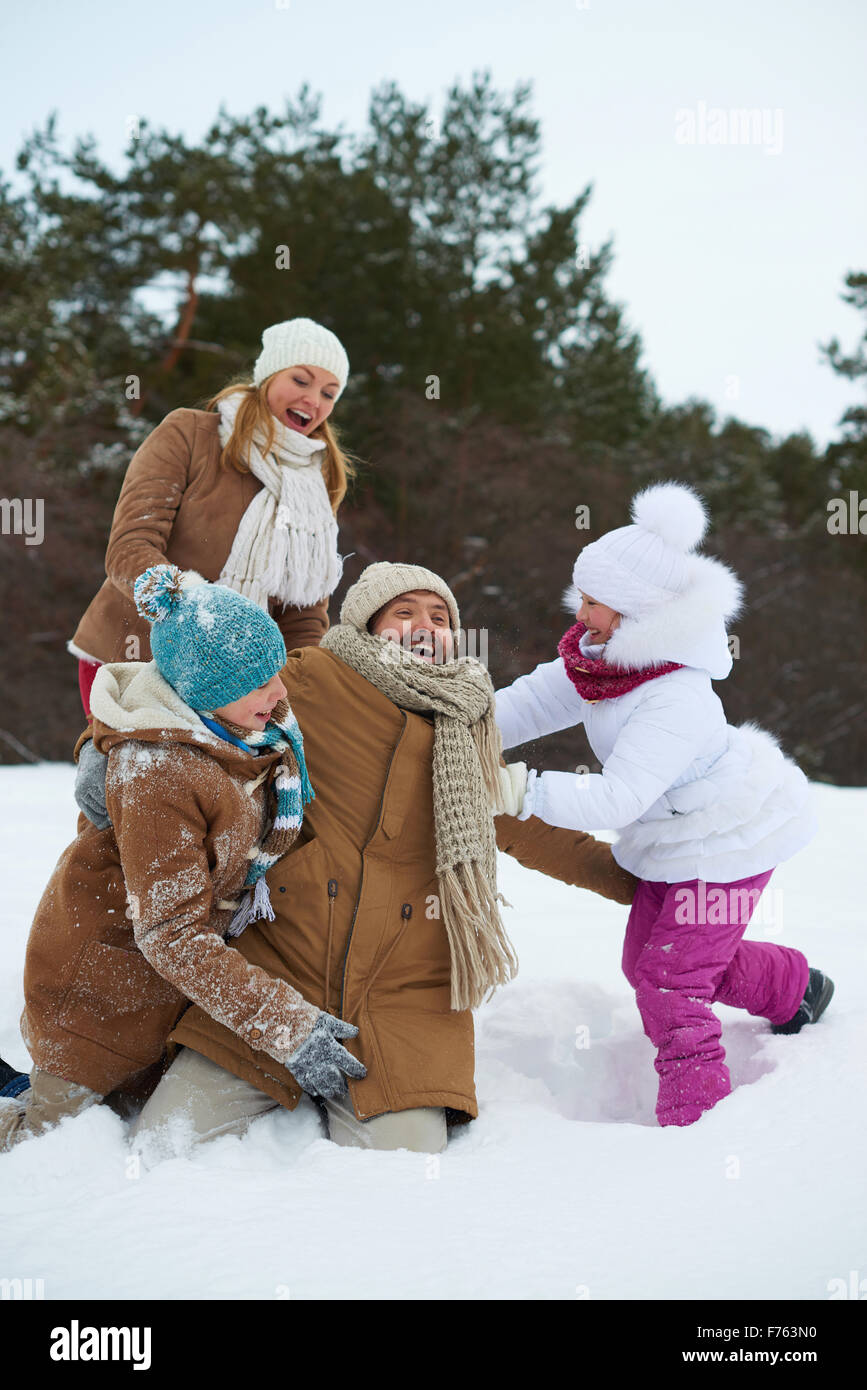Cheerful kids and parents having fun in snowdrift - Stock Image