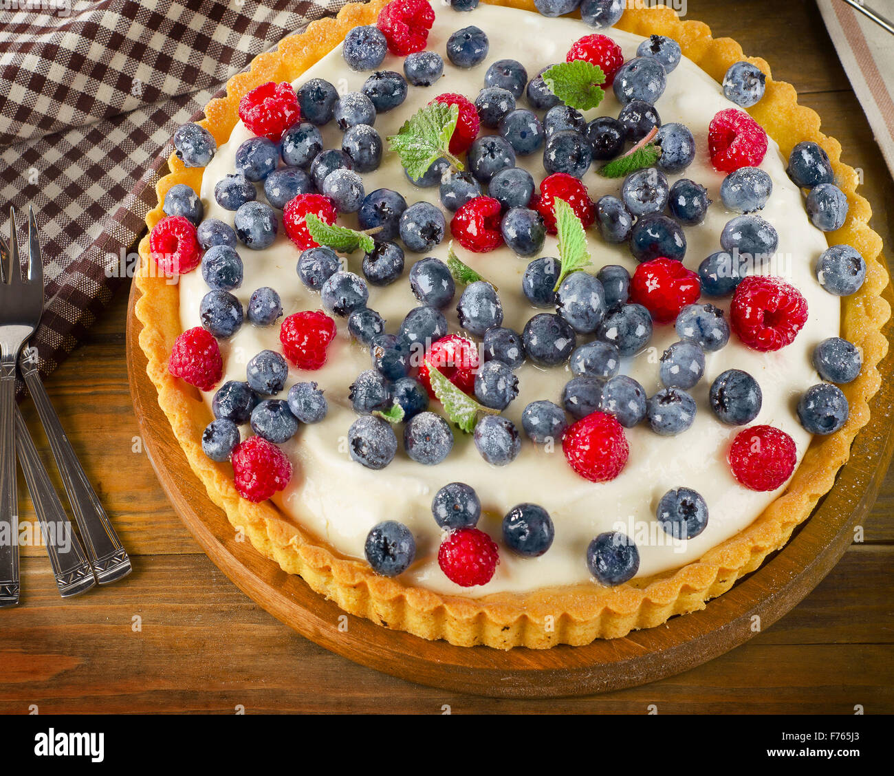 Cheese Cake with fresh berries and mint leaves. - Stock Image