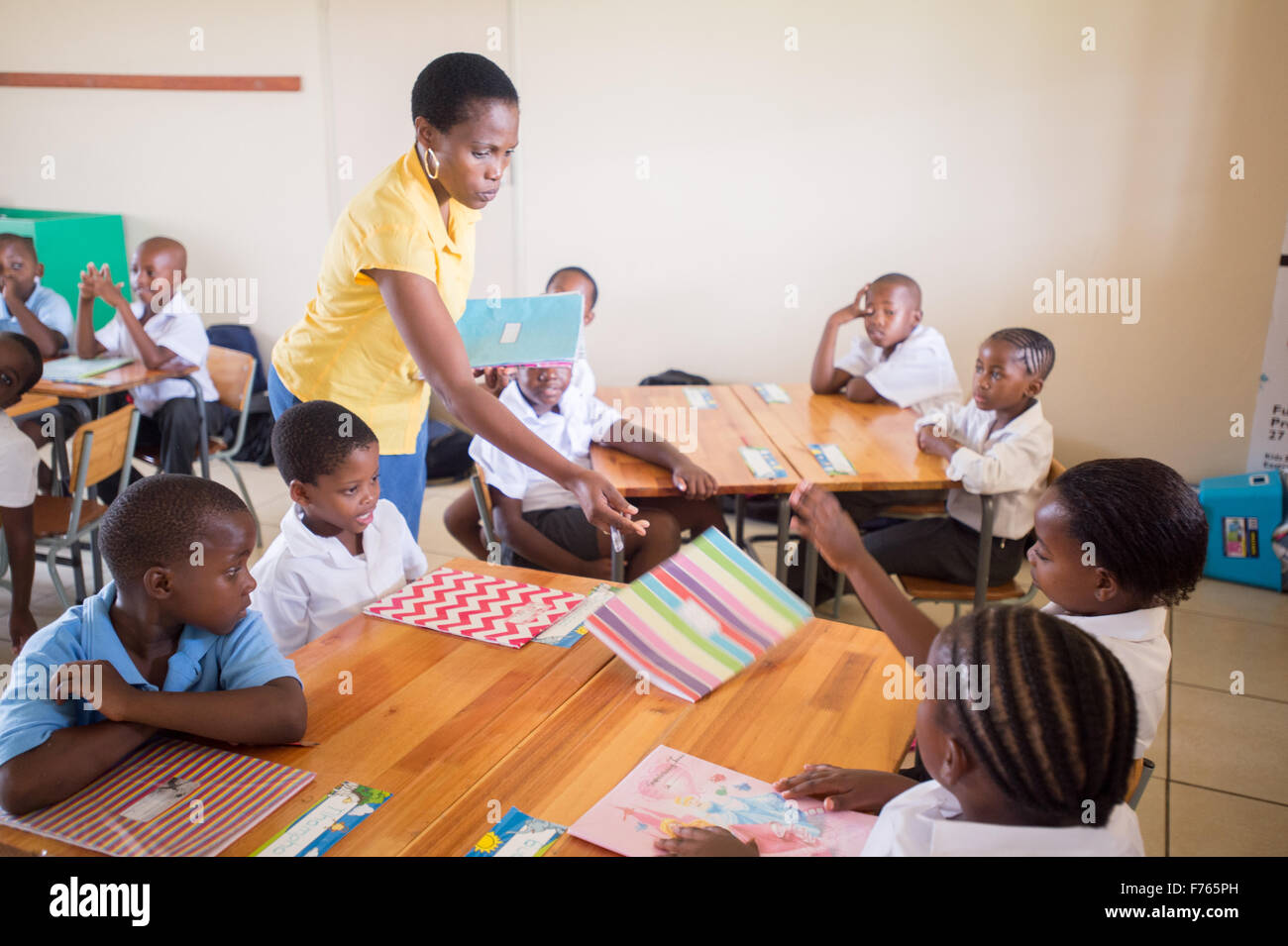SOUTH AFRICA- Teacher handing out folders in classroom. - Stock Image