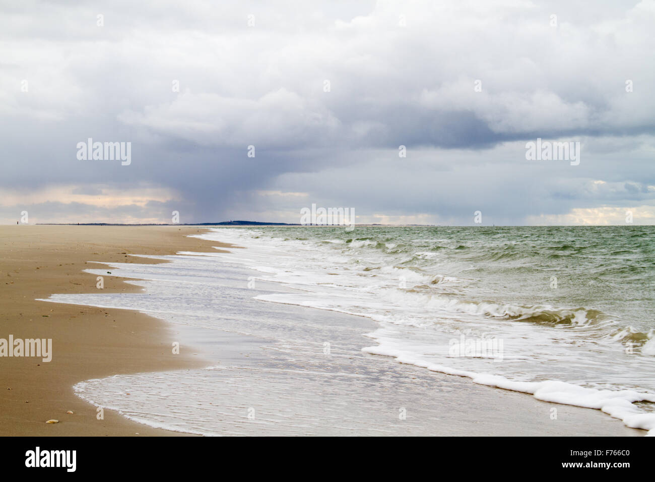 Surfs on the beach, in the distance a rain cloud - Stock Image