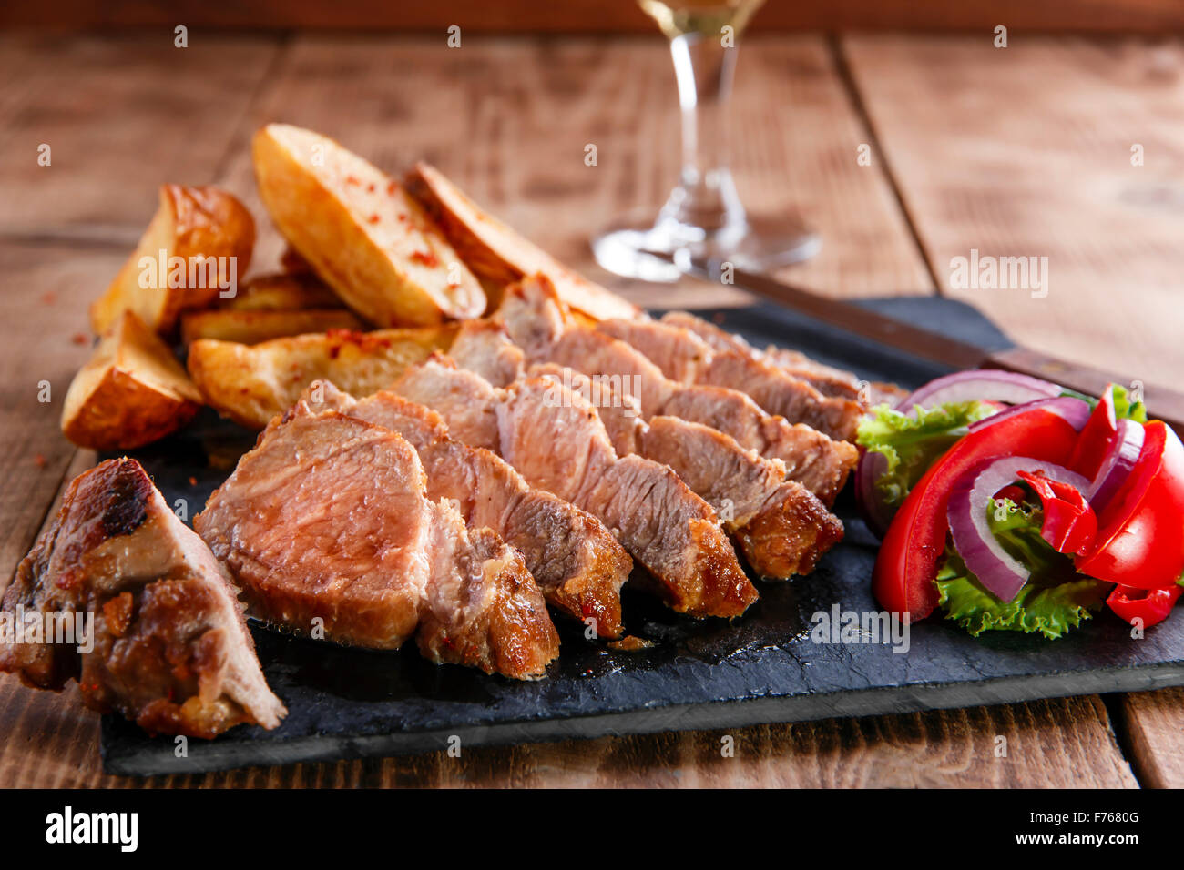Sliced pork steak with fried potatoes - Stock Image