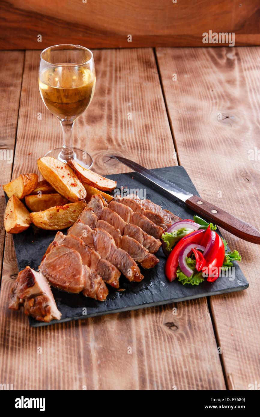 Sliced pork steak with fried potatoes - Stock Image