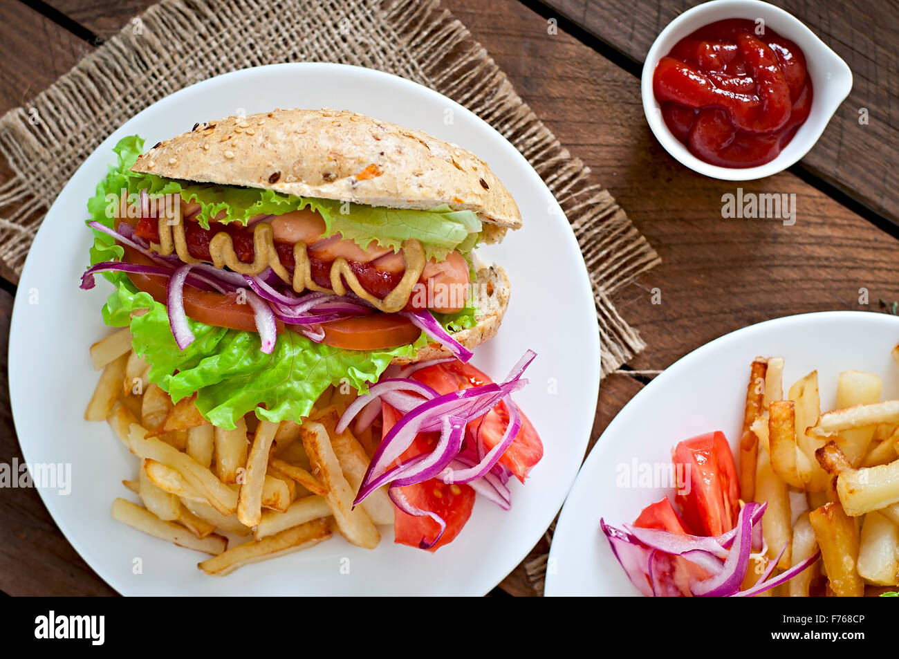 Hot Dogs - sandwich with French fries on white plate - Stock Image